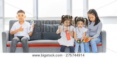Asian Kids Sitting On Grey Sofa And Hold Bottles Of Drink In Their Hand, Concept For School Or Home.