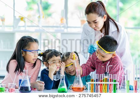 Science Teacher Teach Asian Students In Laboratory Room, Boy Drop Something Into Orange Tube, Colorf