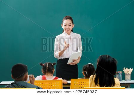 In Classroom, Asian Teacher Stand In Front Of Class And Teaches Students, Students Listen To Her Con