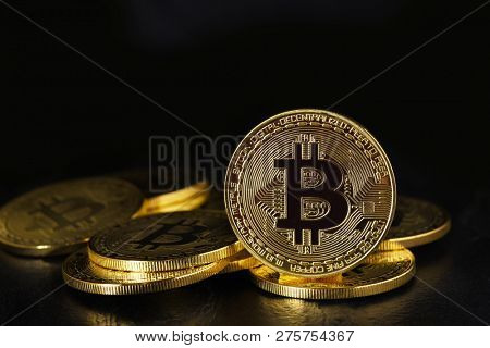 Bitcoin: A pile of physical bit coins, aslo called Digital Currency or Cryptocurrency, with one standing on edge on black with reflection and copy space.