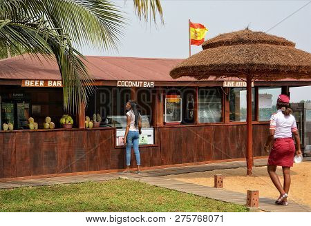 Girl Buys Food In An Open-air Bar At A Beach Resort. Coconut Bar. Travel And Vacation In West Africa