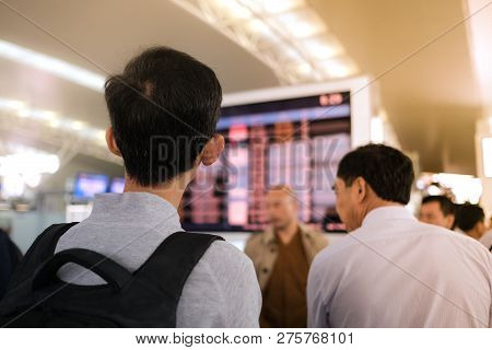 A Man With Backpacker Looking For Information On Electronic Information Board And Departure Board In
