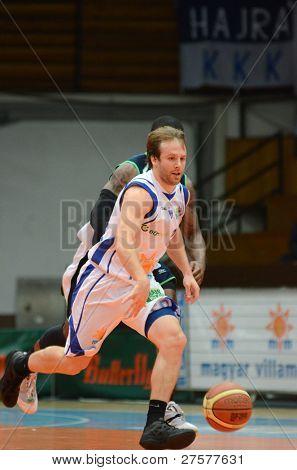 KAPOSVAR, HUNGARY - DECEMBER 10: Josh Wilson (in white) in action at a Hungarian Championship basketball game Kaposvar (white) vs. Szeged (blue) on December 10, 2011 in Kaposvar, Hungary.