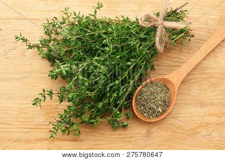 Green Thyme Bunch With Dried Thyme Seeds On Wooden Background. Top View