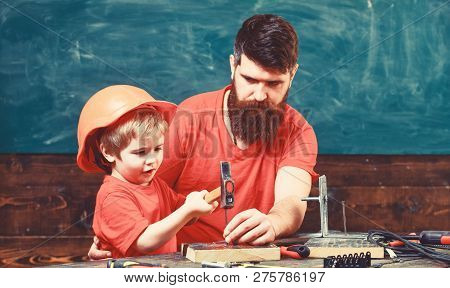 Father With Beard Teaching Little Son To Use Tools, Hammering, Chalkboard On Background. Little Assi