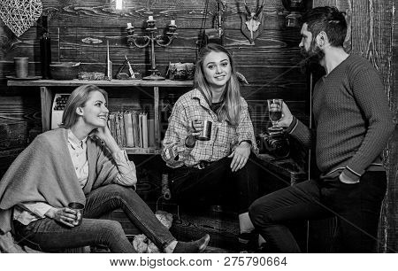 Family enjoy conversation in gamekeepers house. Friends, family spend pleasant evening, interior background. Sincere conversation concept. Girls and man on happy faces hold metallic mugs, talking poster