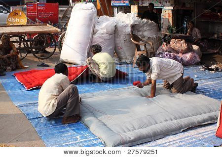 Indian workers manufacturing coverlets.