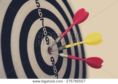 Side View Of A Dartboard With Three Darts In The Bulls Eye. Well-aimed Dart Throwing. A Marksmans Tr