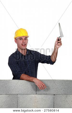 Stonemason holding up a trowel