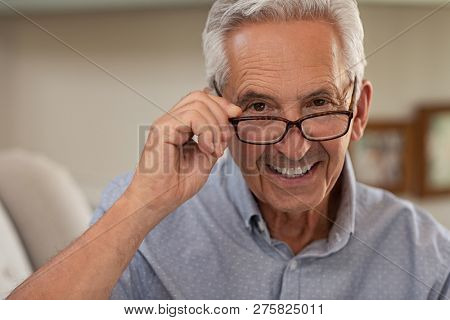Portrait of happy mature man wearing spectacles and looking at camera. Old man smiling with glasses at home. Closeup face of elder trying new eyeglasses.