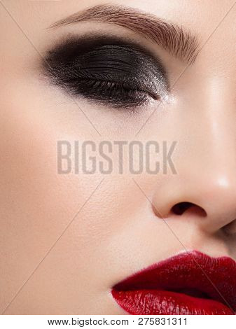 Close-up Of The Beauty Of Half A Woman's Face With Creative Fashion Evening Makeup. Black Smoky Eyes