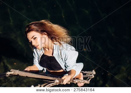Ambition Is Her Only Stimulus. Sensual Woman Hang On Rope Over Water Surface. Sexy Woman Climbing Up