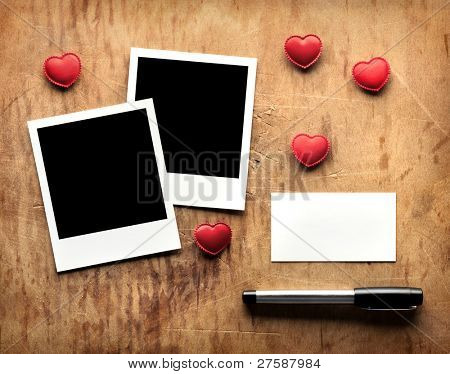 Blank instant photos and small red hearts with blank business (visit) card and fountain pen on old dark grunge background. Romantic theme.