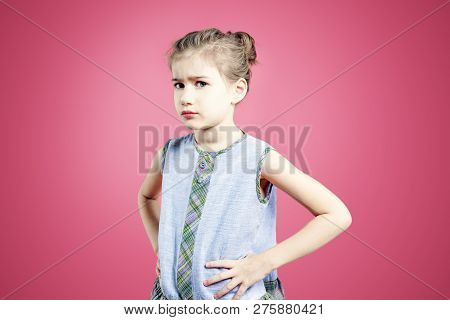 Pouting angry offended child girl over pink background. poster