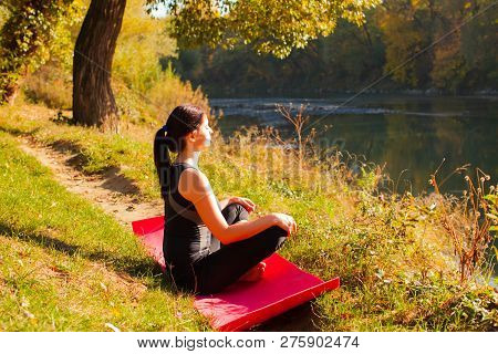 Portrait Of Young Woman Meditating In The Sunlight