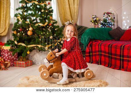 Little Girl Swings On The Rocking Hors