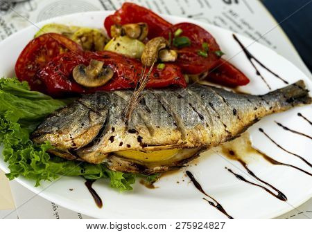 Fried Fish With Grilled Tomatoes And Lemon. Small Depth Of Field