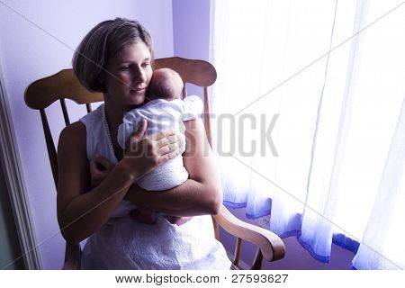 Mother holding newborn baby in rocking chair next to window