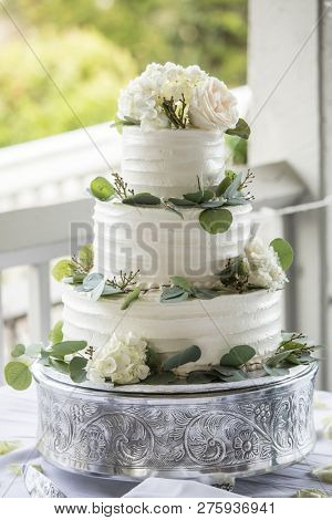 Three tiered wedding cake with buttercream icing and flowers