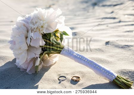 Wedding rings and bouquet of peonies on the beach.