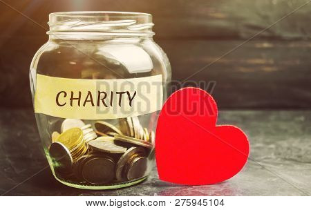 Glass Jar With The Words Charity And The Heart. The Concept Of Accumulating Money For Donations. Sav