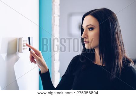 Brunette Woman Entering Security Pin On Home Alarm Keypad.