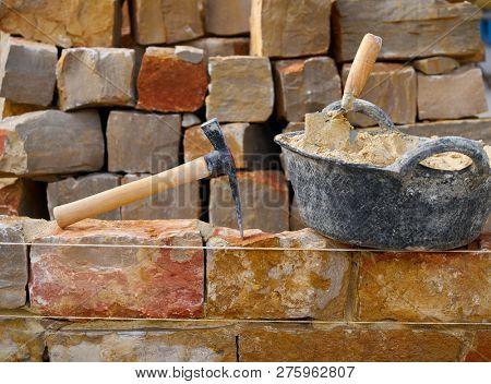 Masonry stone wall construction with mortar and brick hammer trowel tools DIY