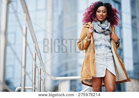 Attractive Curly African American Woman In Brown Coat Posed Near Railings Against Modern Multistory