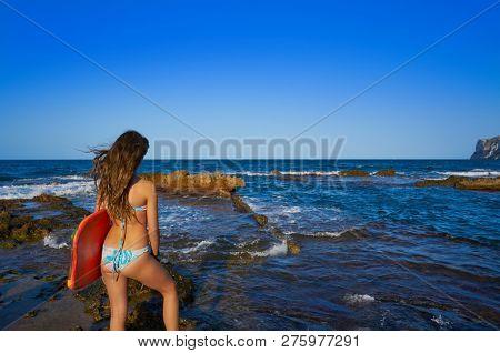 Bikini girl hording surf board in Denia beach of Las Rotas of Spain