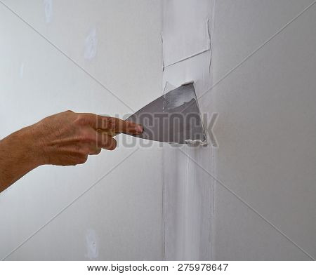 laminated plasterboard plastering join detail spatula and hand