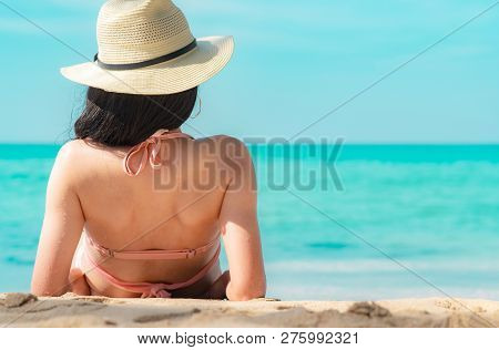 Back View Of Happy Young Asian Woman In Pink Swimsuit And Straw Hat Relax And Enjoy Holiday At Tropi