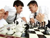 Two men with papers looking at each other aggressively while playing chess poster