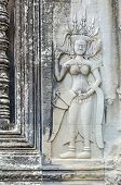 Bas-relief showing devata, the female divine carved figurine, with crown, necklaces, armbands, belts and ankle bands adorning the walls of the main complex of Angkor Wat poster