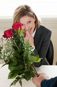 Excited and surprised businesswoman receiving red roses - Valentine's day, Birthday or Anniversary poster