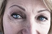 Close-up of mature woman blue eyes poster