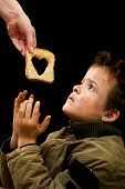 Feeding the poor concept with dirty kid receiving slice of bread - on black poster