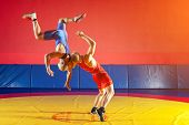 Two strong wrestlers in blue and red wrestling tights are wrestlng and making a suplex wrestling on a yellow wrestling carpet in the gym. Young man doing grapple. poster