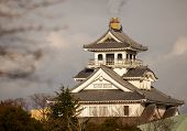 Smokestack emits gas behind traditional white Japanese castle poster