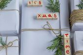 """Top view of white handcraft gift boxes with """"It's x mas time"""" text (wooden letters) and fresh fir branches on white background, seasonal celebration and eco-friendly concept poster"""