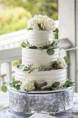 Three tiered wedding cake with buttercream icing and flowers poster