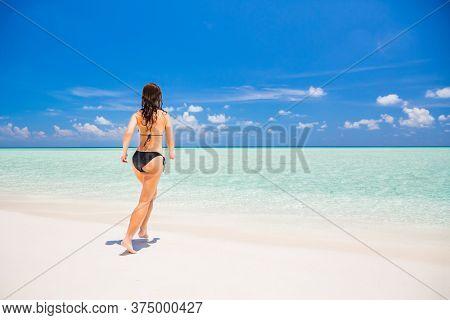 Young woman in bikini enjoing the beautiful ocean beach on Maldives