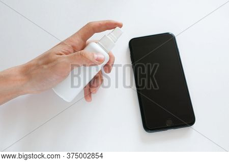 Hand Of Woman Is Spraying Alcohol, Disinfectant Spray On Mobile Phone, Prevent Infection Of Covid-19