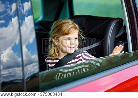 Adorable Toddler Girl Sitting In Car Seat And Looking Out Of The Window On Nature And Traffic. Littl
