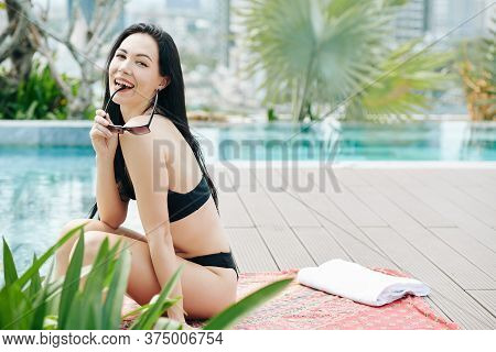 Attactive Happy Young Woman Biting Sunglasses Frame And Looking At Camera When Relaxing At Swimming