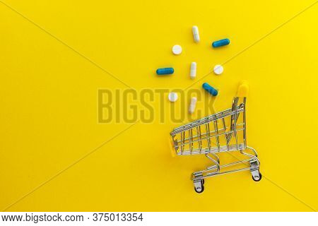 Mini Shopping Cart, Pills And Capsules On Yellow Background. Online Drugstore. Pharmaceutical Indust