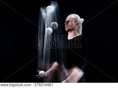 Juggler Throws Balls In Motion And Smoothed White Lines. Isolated On Black