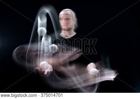 Abstract Image Of Juggler With Smoothed White Balls In Motion