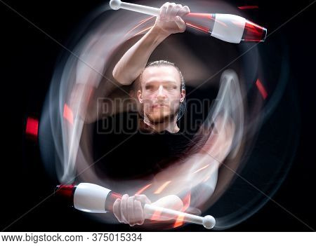 Abstract Image Of Juggler With Smoothed Clubs In Motion Isolated On Black