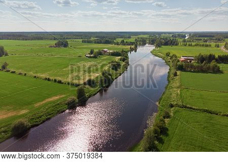 The River Runs Through The Green Fields Of The Rural Finland.