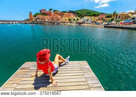 Caucasian Woman Resting And Sunbathing Over Jetty In Rio Marina Harbor Of Elba Island In Red Suit. L